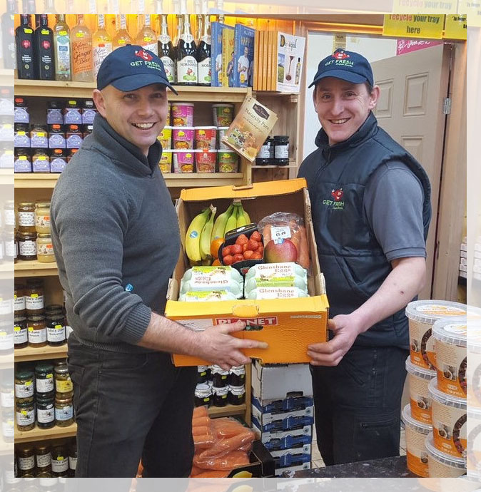 A picture of two staff at Get Fresh Super Foods holding a cardboard tray of fruit, veg and eggs